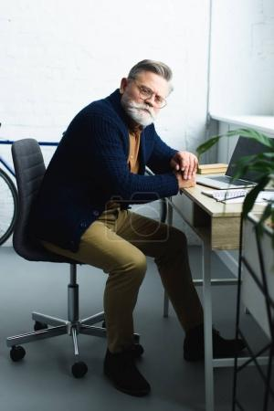 bearded senior man in eyeglasses using laptop and looking at camera