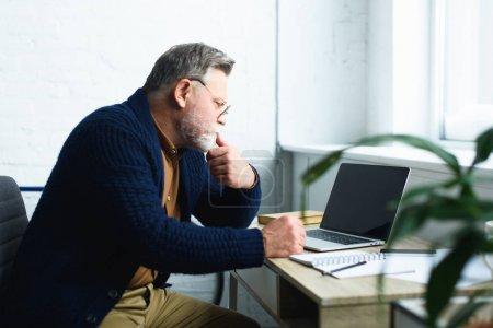 Photo pour Vue latérale de l'homme âgé concentré dans les lunettes à l'aide d'un ordinateur portable avec écran vierge - image libre de droit
