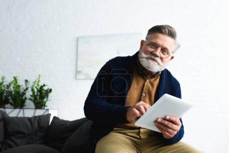 Photo pour Beau barbu senior dans les lunettes tenant tablette numérique et souriant à la caméra - image libre de droit