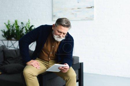 Photo pour Bel homme âgé barbu assis sur le canapé et utilisant une tablette numérique à la maison - image libre de droit