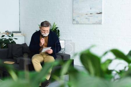 Photo for Selective focus of bearded senior man taking notes while sitting on sofa at home - Royalty Free Image