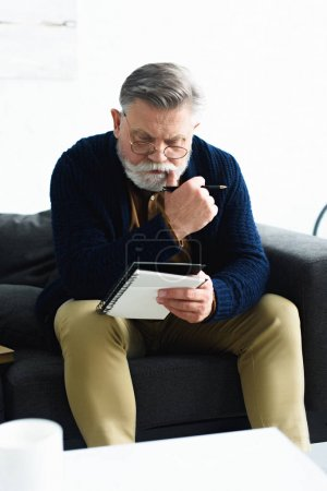 serious senior man in eyeglasses holding pen and notebook while sitting on sofa