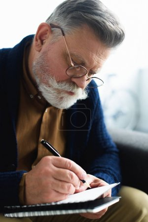 close-up view of concentrated senior man in eyeglasses writing in notebook