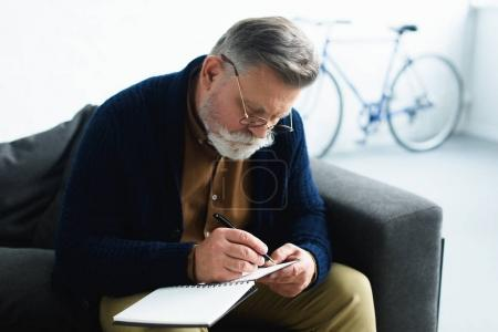 Photo for Focused senior man in eyeglasses taking notes on notebook - Royalty Free Image