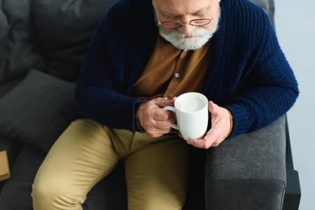 Photo for Cropped shot of bearded senior man in eyeglasses holding cup while sitting on sofa - Royalty Free Image