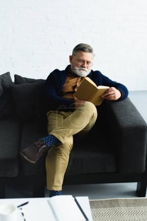 stylish bearded man reading book on sofa at home