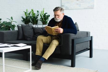 Photo pour Sérieux homme âgé barbu assis sur le canapé et le livre de lecture à la maison - image libre de droit