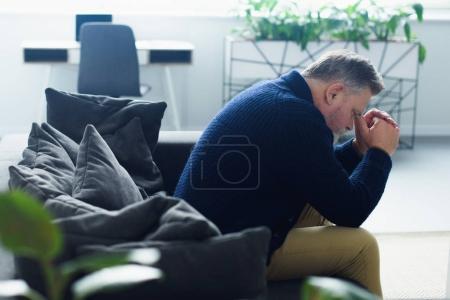 Photo pour Vue latérale de l'homme âgé bouleversé assis sur le canapé à la maison - image libre de droit