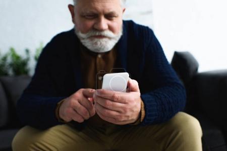 Photo pour Plan recadré d'un homme âgé souriant utilisant un smartphone assis à la maison - image libre de droit