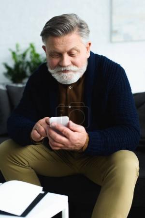 Photo pour Beau homme âgé souriant utilisant un smartphone tout en étant assis à la maison - image libre de droit