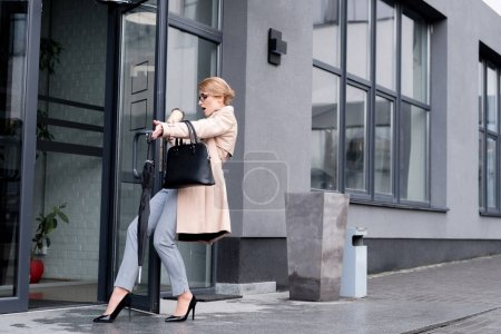 stylish businesswoman with falling disposable cup of coffee entering business center