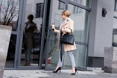 stylish businesswoman in coat with coffee to go entering business center