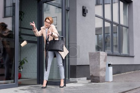 businesswoman with falling disposable cup of coffee talking on smartphone while entering business center