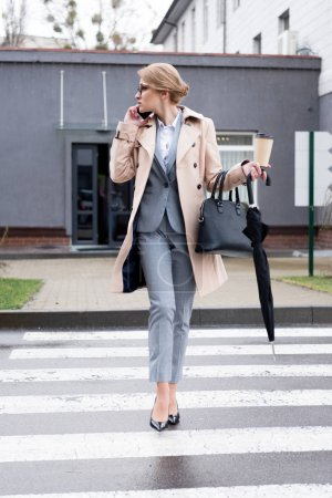 businesswoman with coffee to go and umbrella talking on smartphone while crossing road on street