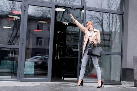 businesswoman talking on smartphone near business center