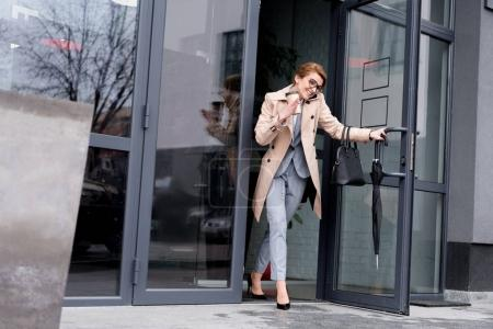 smiling businesswoman talking on smartphone while exiting business center