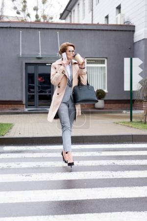 businesswoman talking on smartphone and drinking coffee while crossing road on street