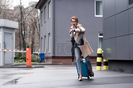 hurrying businesswoman with suitcase checking time and running on street