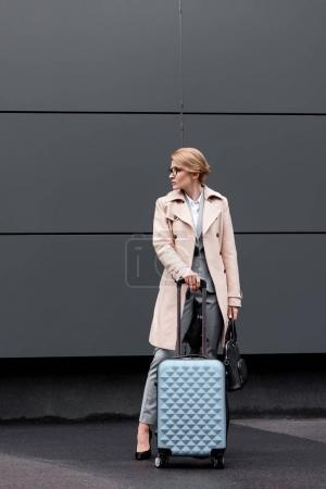 stylish businesswoman in coat with suitcase waiting for taxi on street