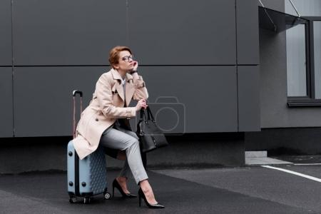 businesswoman in stylish coat sitting on suitcase while waiting for taxi on street