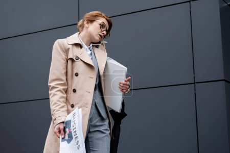 businesswoman with documents talking on smartphone on street