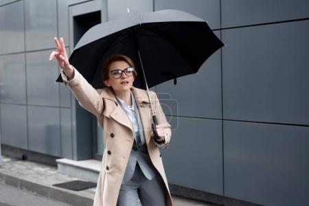 businesswoman in stylish coat with umbrella calling for taxi on street