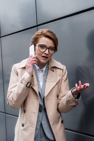 Photo pour Portrait de femme gesticulant parler sur smartphone sur rue - image libre de droit