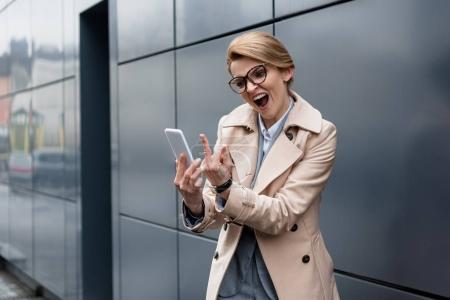 Photo pour Portrait de femme d'affaires avec smartphone montrant majeur sur la rue - image libre de droit