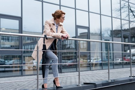 businesswoman in stylish coat standing on street