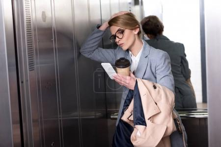 portrait of unsatisfied businesswoman in suit with smartphone in elevator