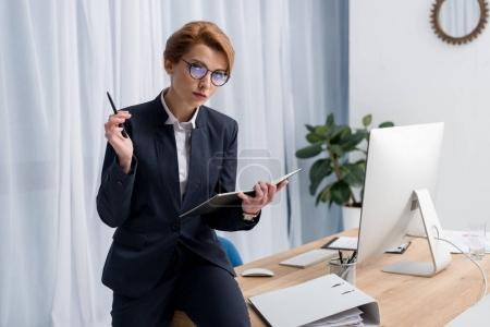 portrait of businesswoman in eyeglasses with notebook at workplace in office