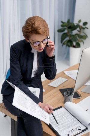 businesswoman looking at contract while talking on smartphone at workplace in office