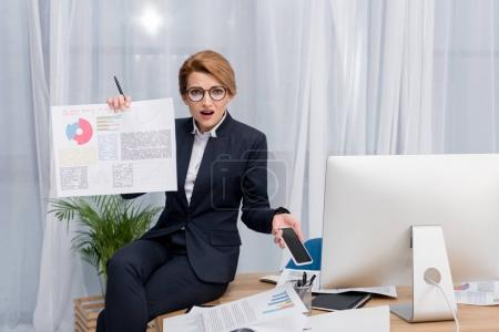 confused businesswoman with document and smartphone at workplace in office