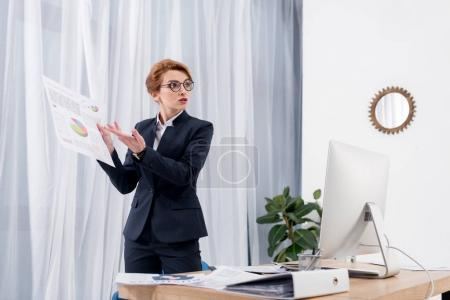 businesswoman pointing at documents while talking with colleague at workplace in office