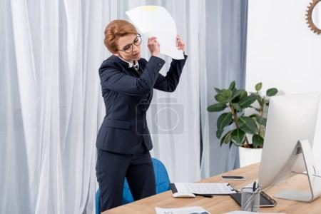 emotional businesswoman throwing documents at workplace in office