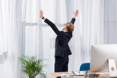 Photo for Side view of businesswoman in suit stretching and looking out window in office - Royalty Free Image