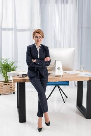 smiling businesswoman with arms crossed leaning on table in office