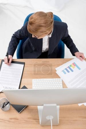 overhead view of businesswoman doing paperwork at workplace in office