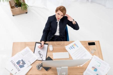 Photo for Overhead view of overworked businesswoman at workplace in office - Royalty Free Image