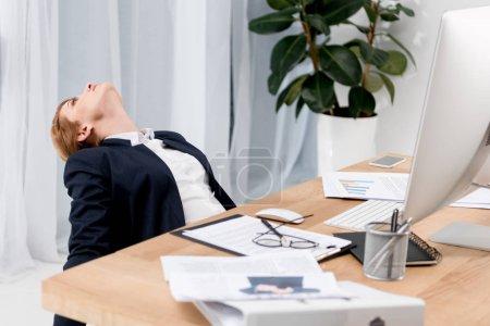 Photo pour Femme d'affaires fatigué en costume au milieu de travail avec des documents au bureau - image libre de droit