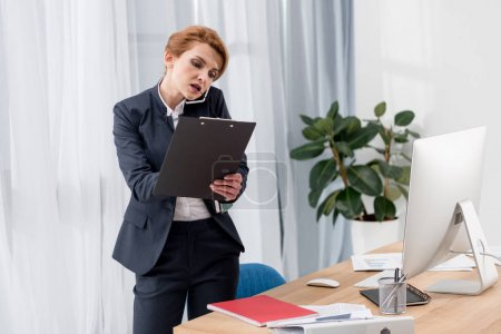 Photo for Businesswoman with documents talking on smartphone at workplace in office - Royalty Free Image