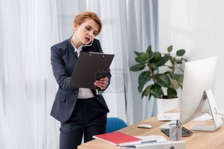 Photo pour Femme d'affaires avec des documents parlant sur smartphone au lieu de travail au bureau - image libre de droit