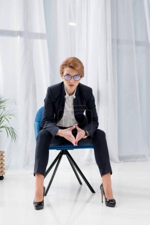 Photo pour Confiant femme d'affaires en costume et lunettes assis sur la chaise de bureau - image libre de droit