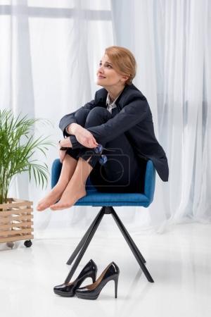 Photo pour Femme d'affaires surmené en costume assis sur la chaise de bureau - image libre de droit