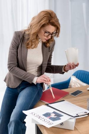Photo pour Concentré de femme d'affaires avec boîte de cuisine asiatique, faire de la paperasse sur lieu de travail au bureau - image libre de droit