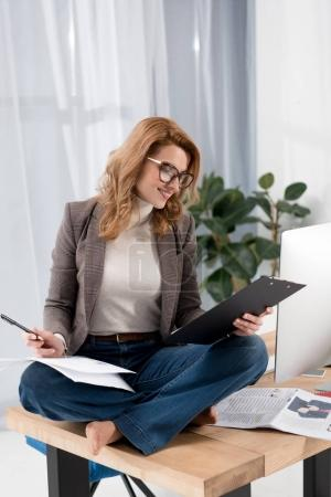 smiling businesswoman in eyeglasses doing paperwork while sitting on table in office