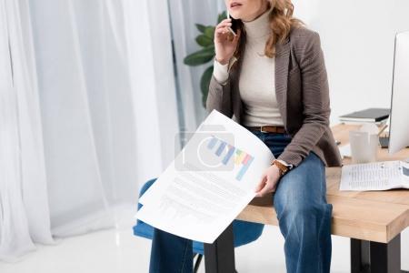 Photo pour Plan recadré de femme d'affaires avec des papiers parlant sur smartphone tout en étant assis sur la table dans le bureau - image libre de droit