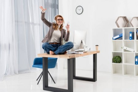 businesswoman in headphones with smartphone listening music on table in office