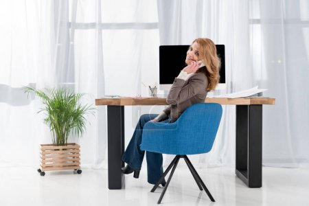 smiling businesswoman talking on smartphone at workplace in office