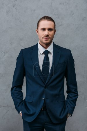 Photo for Young handsome businessman in stylish suit in front of concrete wall - Royalty Free Image